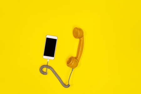 Mobile phone and old fashioned handset on yellow background. Modern retro style. New old technology.