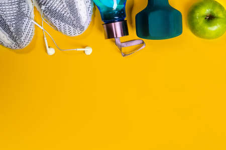 Fitness equipment and space for text on bright yellow background. Sport lifestyle concept with sneakers, dumbbell, bottle of water, apple, tennis ball and headphones. Copy space, flat lay. Top view.