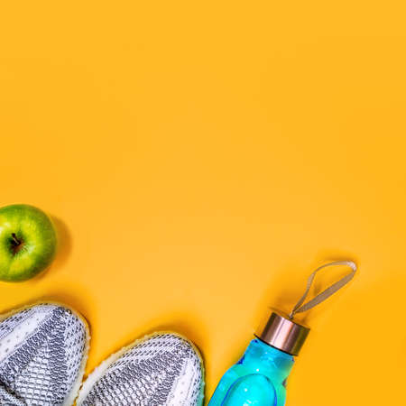 Top view to composition with fitness equipment and space for text on yellow background. Sport lifestyle concept with sneakers, bottle of water and apple. Copy space, flat lay