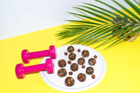 Protein peanut butter energy bites or energy balls. Homemade raw chocolate truffles with nuts on plate with dumbbells and palm leaf on yellow background. 免版税图像