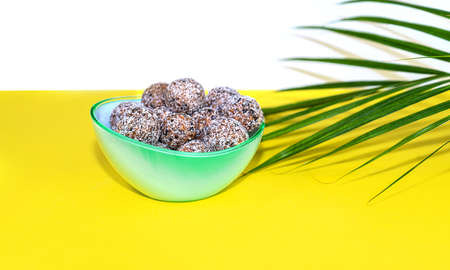 Protein peanut butter energy bites or energy balls. Homemade raw chocolate truffles with nuts and in coconut flakes on plate with palm leaf on yellow background.