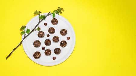 Protein peanut butter energy bites or energy balls. Homemade raw chocolate truffles with nuts and in coconut flakes on plate and yellow background. 免版税图像