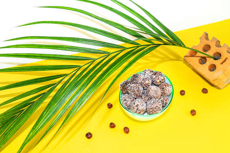 Protein peanut butter energy bites or energy balls. Homemade raw chocolate truffles with nuts on plate with palm leaf on yellow background.