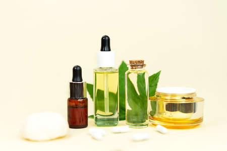 Glass bottles with herbal CBD oil, THC tincture, pills, sponge and hemp leaf on pastel beige background. Flat lay, minimal style. Cosmetics CBD oil. Essential natural oils for face and body. 免版税图像