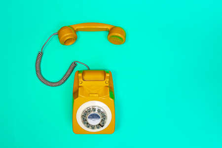 Yellow handset of a telephone on a green mint background. Modern retro style. New old technology. 免版税图像