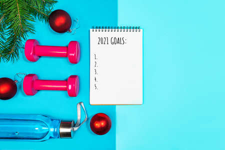 Goals list for New Year Holiday. Christmas sport set with dumbbells, bottle of water, fir tree branches and red balls on blue yoga mat and on pastel blue background. Flat lay, top view, copy space.
