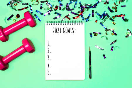 Goals list for New Year Holiday. Christmas sport set with dumbbells, notebook with pen and colorful confetti on on pastel mint green blue background. Flat lay, top view, copy space. Stock Photo