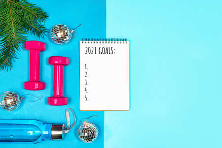 Goals list for New Year Holiday. Christmas sport set with dumbbells, bottle of water, fir tree branches and disco balls on blue yoga mat and on pastel blue background. Flat lay, top view, copy space.