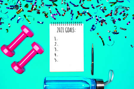 Goals list for New Year Holiday. Christmas sport set with dumbbells, notebook with pen, bottle of waterwater and colorful confetti on mint green blue color background. Flat lay, top view, copy space.