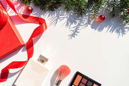 Christmas Beauty Cosmetics Objects and Gift Box with Christmas fir tree branches as holiday background. Close up. Festive Christmas and Happy New Year beauty product concept. Copy Space, flat lay. 版權商用圖片