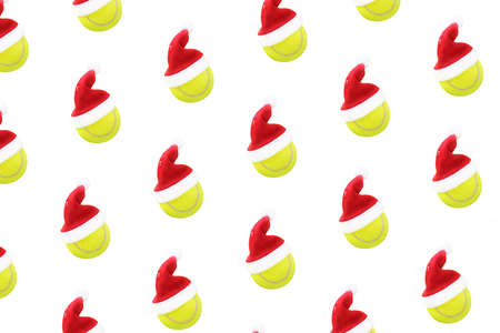 Santa hat on tennis ball pattern on white snow background. Merry Christmas and New year concept with tennis balls. Yellow green color tennis balls, sport lifestyle. Isolated, 版權商用圖片
