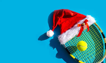 Santa Claus hat on tennis racket and ball on blue background. Merry Christmas and Happy New Year tennis concept. Close up, sport lifestyle, funny. 版權商用圖片