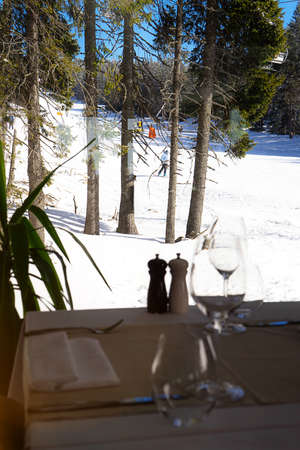 View from the restaurant with glasses of wine to the snowy slopes. Winter holiday concept. Front view. 版權商用圖片