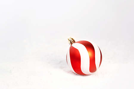 Red white Christmas decoration bauble on snow white background with bokeh. Merry Christmas and Happy New Year concept. Front view. Copy space.