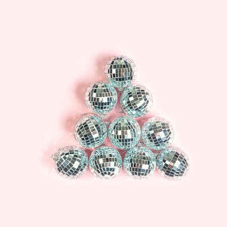 Party Disco balls on pastel pink background. Merry Christmas and happy New Year concept. flat lat, copy space.
