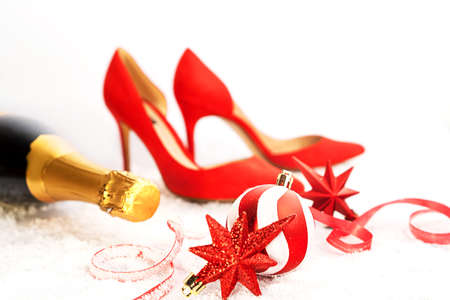 Christmas and New Year party outfit composition with red shoes, holidays decorations, bottle of champagne on white background, isolated. Red white Christmas decoration bauble and red stars with ribbon on snow white background with bokeh. Front view. Copy space.
