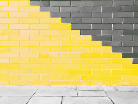 Abstract bright illuminating yellow and gray colours of wall brick as background. Trendy colors of the year 2021 - Gray and Yellow.
