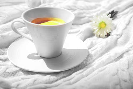 Coffee in white cup and nice white flower on the soft plaid in morning sunlight. Concept of Color of the Year 2021. Illuminating yellow and gray colours background.