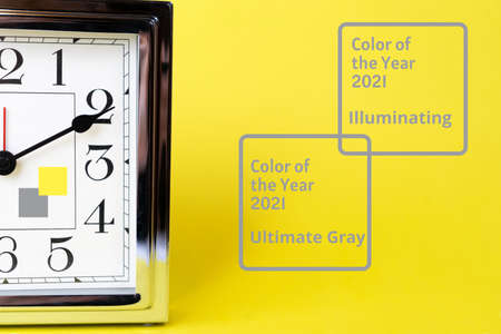 Color of the 2021 time concept with metal gold alarm clock and bright illuminating yellow and gray colours background. Shopping. Sale concept. Flat lay, top view, place for text. Abstract bright illuminating yellow and gray colours background. Trendy colors of the year 2021 - Gray and Yellow. 版權商用圖片