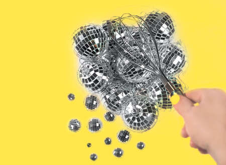 Gray silver Disco balls for decoration party shattering into small balls with whisk in hand on illuminating yellow background. Christmas New year Concept of Color of the Year 2021. 版權商用圖片