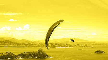 A parachute with skydiver on sunny sky background. Concept of Color of the Year 2021 with bright illuminating yellow and gray colours. Active lifestyle. Extreme sport. Aerial view of Rio de Janeiro.