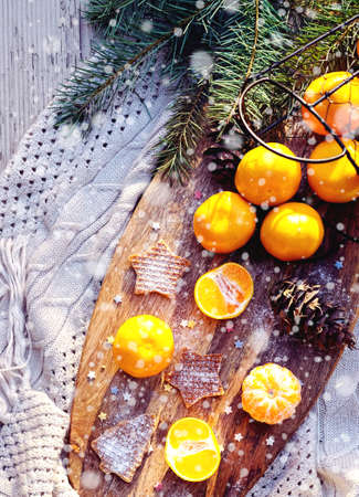 Winter cozy concept: tangerines, waffle cookies, fir tree brunches on wooden kitchen board on gray plaid. Concept of Color of the Year 2021 with bright illuminating yellow and gray colours. Flat lay. 版權商用圖片
