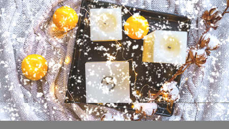 Winter still life composition with cotton, tangerines, candles and snowflakes on gray plaid. Concept of Color of the Year 2021 with bright illuminating yellow and gray colours. Flat lay, copy space 版權商用圖片