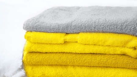 Stack of towels in Color of the Year 2021 - bright illuminating yellow and gray colours on white snow, isolated. Concept of Color of the Year 2021.