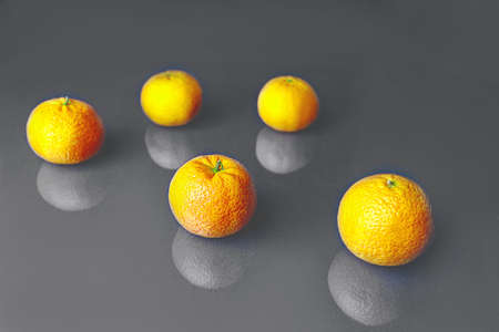 Composition with bright illuminating yellow tangerines on a gray color background. Pattern, copy space. Concept of Color of the Year 2021.