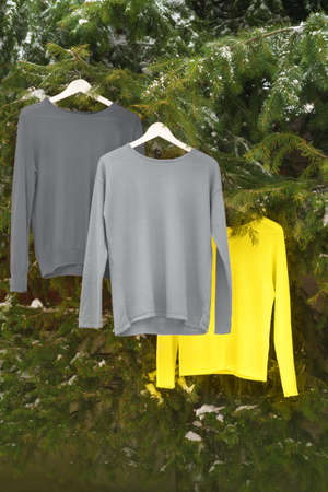 Clothes on hangers in the colors of the year 2021 - bright illuminating yellow and gray colours. Sweaters, sweatshirts in trendy colors of the year 2021 - Gray and Yellow. Fashionable clothes.
