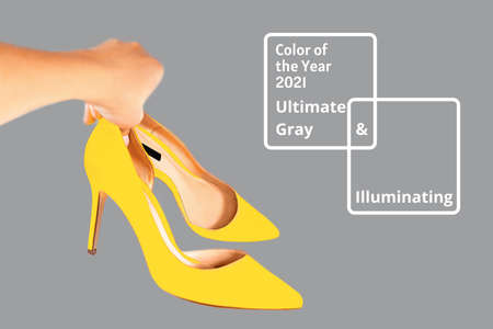 Bright illuminating yellow high heel shoes in womans hand on gray color background. Concept of Color of the Year 2021. Fashion outfit abstract layout. Front view, copy space. Valentines day concept. 版權商用圖片