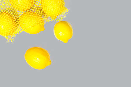 Creative layout made of bright illuminating yellow lemons on gray color background. Flat lay, close up.