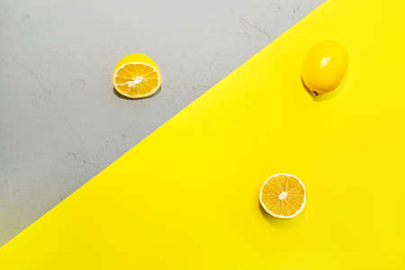 Composition with lemon on yellow and gray concrete background. Christmas, New year, Valentines day, shopping layout. Concept of Color of the Year 2021. Flat lay, top view copy space. 版權商用圖片