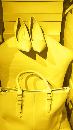 Bright illuminating yellow high heel shoes, handbag and glasses on gray color background. Concept of Color of the Year 2021. Fashion outfit abstract layout. Valentines day concept.