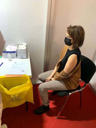 Female waiting the vaccination injection in medical mask. Global vaccination. Virus protection.