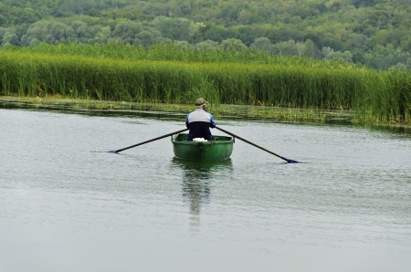 Fisherman in a boat on water returns ashore after fishing on a background a thick reed   photo