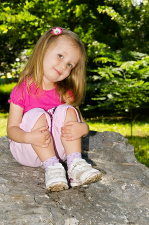 Portrait of girl on an enormous stone on a background green trees. Stock Photo