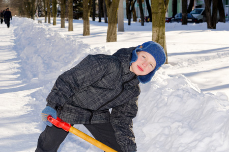 Boy with a shovel after a snow fall on boulevard in a frosty day.