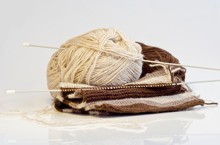 Two coil of yarn and knitting needles on a white background
