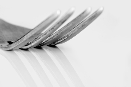 Tines of a fork with reflection on a glossy surface