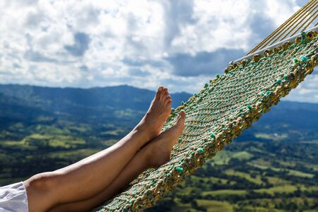 Rest beyond the clouds or woman sleeps on hammock on the mountain