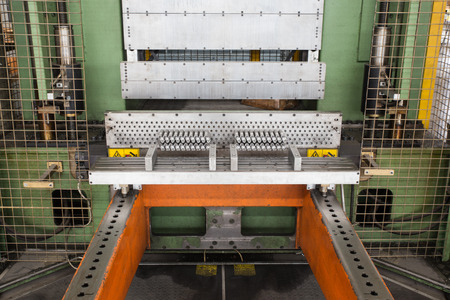 forming: detail of press to build aluminum batteries Stock Photo