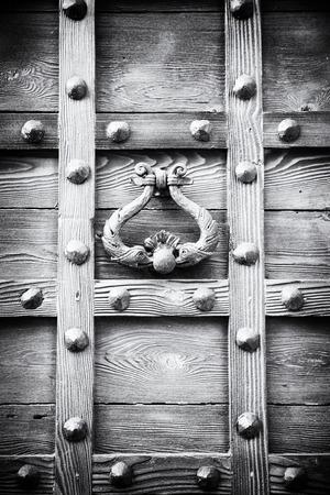 ancient door knocker of a medieval wooden portal