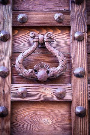 ancient door knocker of a medieval wooden portal photo