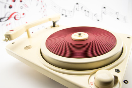 composition with vintage red record player and musical notes on background photo