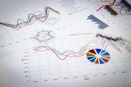 informe: pila de documentos en papel con los informes financieros y datos de información estadística aisladas sobre fondo blanco Foto de archivo