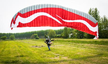motorizado: hombre con parapente motorizado roja despega de un campo verde