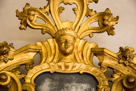 antique mirror: detail of a carved gilded frame of an antique mirror Stock Photo
