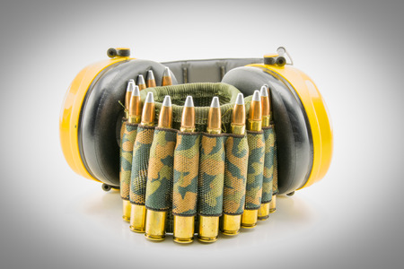 decibel: yellow ear protection and camouflage ammunition belt for rifle