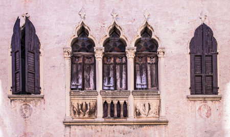 old windows: old windows on a medieval palace facade in Verona, Italy